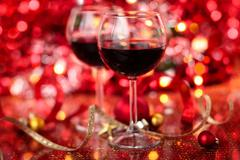 Red wine in wineglasses  against holiday lights background - stock photo