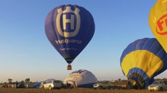 Inflating and fly away on hot-air balloons at sunrise during Hot Air Balloon Fes Arkistovideo