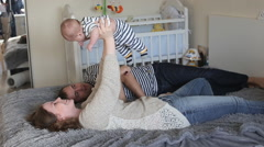 Parents dad mom playing with baby son Stock Footage