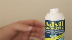 Hand takes two pills of Advil out from container Stock Footage