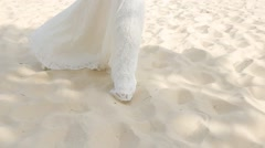Happy bride in a white long gown walking barefoot along the beach in sunny day Stock Footage