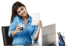 Portrait of a smiling businesswoman with coffee cup in front of laptop in a b - stock photo