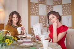 Two women in the kitchen drinking tea Stock Photos