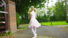 4K Happy little girl with lots of energy practising ballet moves in the garden Stock Footage