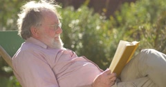 Retired elderly man relaxing outdoors reading a book enjoying retirement Stock Footage