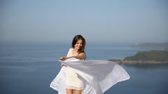 Young enjoying woman with Fluttering white curtains at the open air above sea Stock Footage