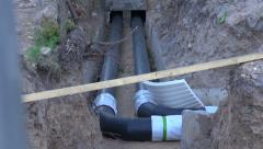 Two black water heating pipes in a ditch going into the house Stock Footage
