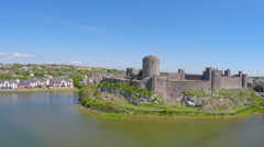 A beautiful rising aerial shot reveals Pembroke Castle in Wales. - stock footage