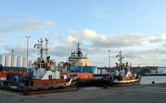Vessels docked at Aberdeen Harbour with storage tanks behind - stock photo