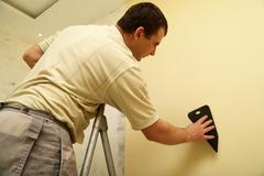 Worker glues new wallpaper - stock photo