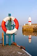 White and Red Life Buoy in Harbour with Lighthouse Stock Photos