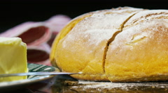 4K Close up of knife slicing into a loaf of fresh bread Stock Footage