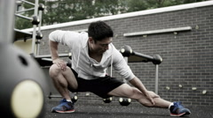 4K Very fit Asian man stretching out in outdoor urban environment. - stock footage