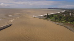 Aerial track down flooded river towards  sea Stock Footage