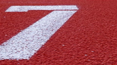 Slow dolly of a number 7 on a running track, counter number seven Stock Footage