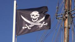 Black pirate flag waving on sunny windy day Stock Footage