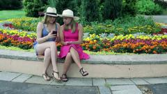 Shocked girlfriends looking at something on smartphone in the park Stock Footage