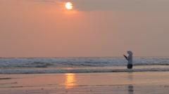 Fisherman in surf at sunset,Kuta,Bali,Indonesia Stock Footage