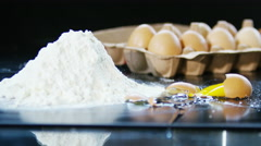 4K Fresh egg in the shell dropping and breaking beside a heap of flour - stock footage