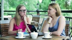 Girlfriends talking and add sugar too coffee in cafe Stock Footage