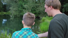 4K Man and young boy spending time together and fishing at lake Stock Footage
