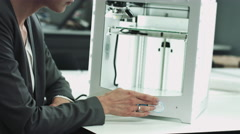 Female designer looking at 3D printed object in studio Stock Footage