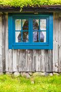 Ancient Swedish wooden farmhouse with blue window - stock photo