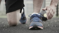 4K unrecognisable man in urban area ties his shoelaces during workout - stock footage