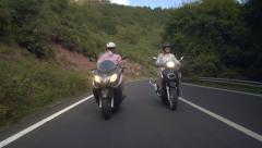 Front view of a couple of scooter riders on country road - stock footage