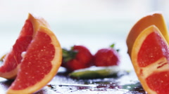 4K Quarter sections of a fresh pink grapefruit falling onto work surface Stock Footage