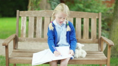 4K Portrait of happy little girl doing her homework outdoors in the garden Stock Footage