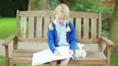 4K Portrait of happy little girl doing her homework outdoors in the garden - stock footage