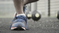 4K unrecognisable man in urban area ties his shoelaces during workout Stock Footage