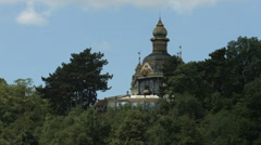 View of a decorated tower surrounded by trees in Prague Stock Footage