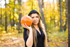 beautiful witch holding pumpkin. Halloween, masquerade - stock photo