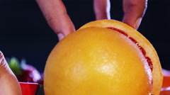 4K Close up on hands cutting a fresh pink grapefruit into 2 pieces - stock footage