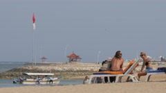 Tourists in beach chair, while boat returns,Sanur,Bali,Indonesia Stock Footage