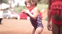 A cute little girl being sprayed with a hose and running away Stock Footage