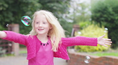 4K Cute little girl having fun playing with bubbles in the garden - stock footage