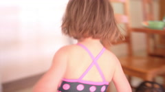 Little girl in a swimsuit runs around the kitchen table Stock Footage
