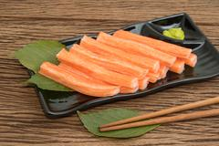 Imitation Crab Stick  in plate on wooden  background - stock photo