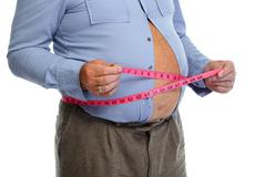 Fat man belly with measuring tape. - stock photo