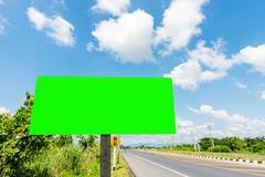 billboard green screen roadside with blue sky - stock photo
