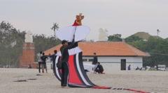 Men lauching long tailed kite,Sanur,Bali,Indonesia Stock Footage