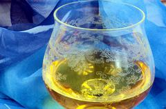 Glass of cognac wrapped in blue cloth, alcohol, decoration, art - stock photo