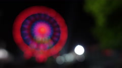 A blurred view of a Colorful illuminated giant ferris wheel Stock Footage