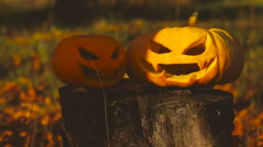 Two scary pumpkin lantern on a stump Stock Footage