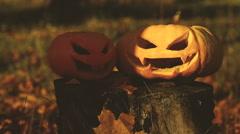 Two scary pumpkin lantern on a stump - stock footage