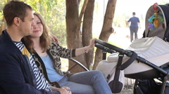 Parents with stroller in park Stock Footage