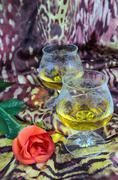 Two glasses of cognac with a red rose on a colored background, alcohol, brown - stock photo